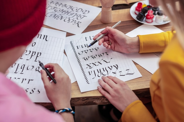 Lettere di pittura. vista dall'alto di due talentuosi studenti di lettere di pittura di scuola d'arte insieme