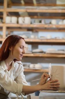 La pittura. una bella donna che sembra coinvolta mentre dipinge il vaso