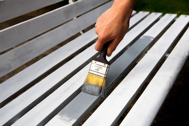 Processo di verniciatura della panca in legno con pennello da pittura.