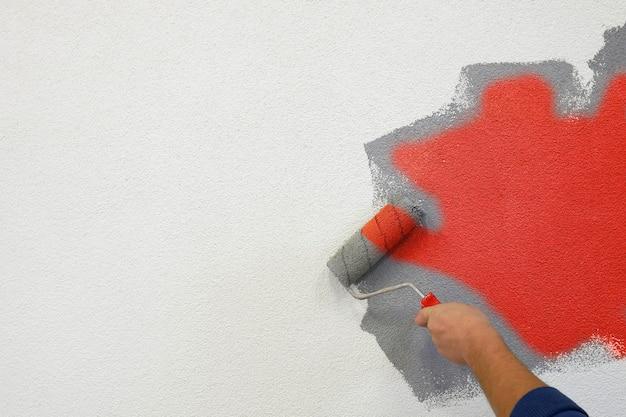 Dipingere i muri con un rullo nella mano sinistra.
