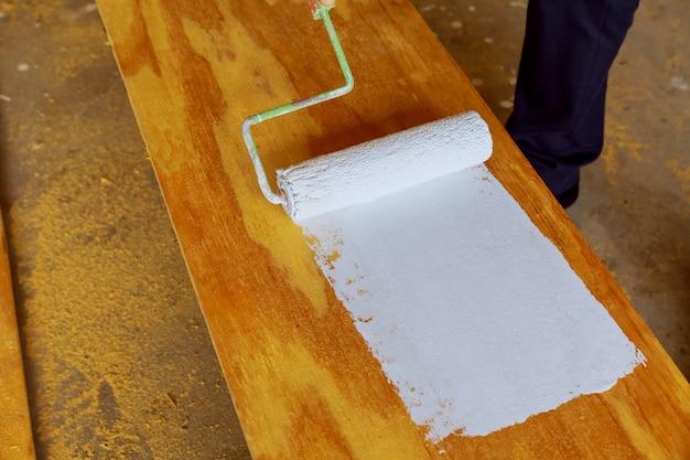 Dipingendo il legno con rullo di vernice bianca