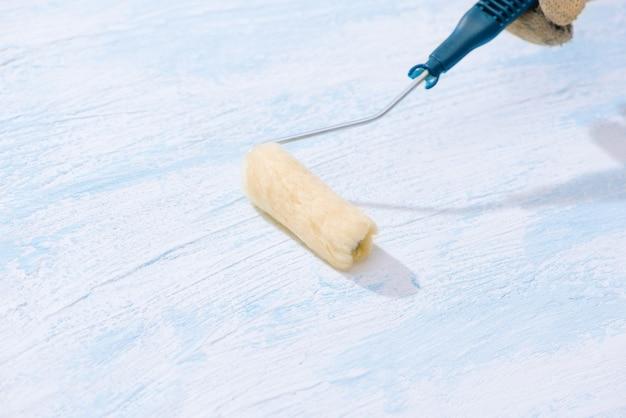 Dipingere su parete di superficie in legno con la spazzola a rullo