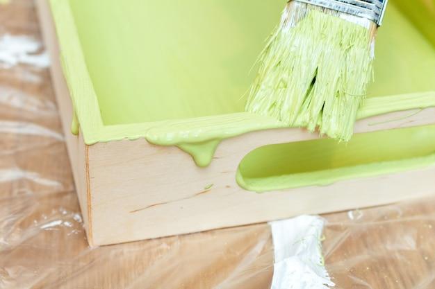 Dipingere un vassoio di legno in un colore verde kaki con un primo piano di un pennello a nappa sullo sfondo