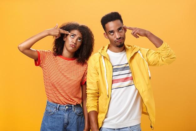 Coppia di amanti afroamericani che si infastidiscono con i genitori che rimproverano insegnando loro come vivere la vita sessuale alzando gli occhi al cielo dall'irritazione tenendo la pistola a dito vicino alle tempie in piedi vicini l'uno all'altro