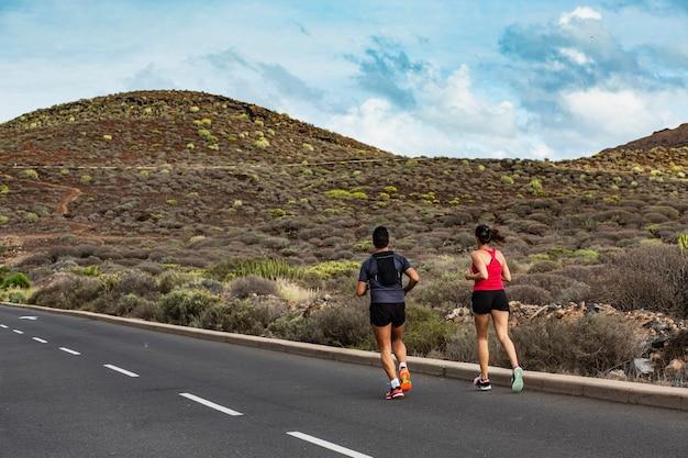 Una coppia di atleti fa jogging lungo la strada in montagna