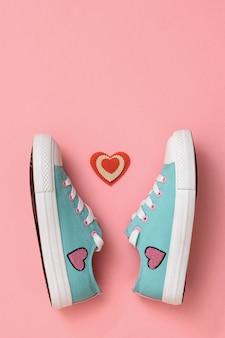 Un paio di bellissime sneakers e un cuore rosso e bianco su una superficie rosa