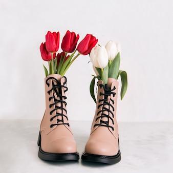 Un paio di scarpe beige con fiori su sfondo bianco. concerto di primavera.