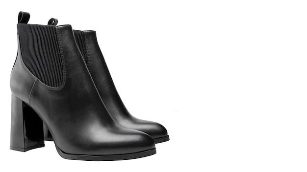 Un paio di eleganti stivali di pelle con tacco alto neri si trova su uno sfondo bianco accanto a un posto per il testo. calzature autunnali di qualità. focalizzazione morbida. isolato su bianco.