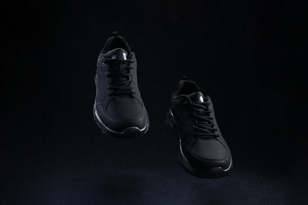 Paio di scarpe da ginnastica senza marchio nere che volano su sfondo scuro. le scarpe da corsa sportive nere levitano nell'aria.