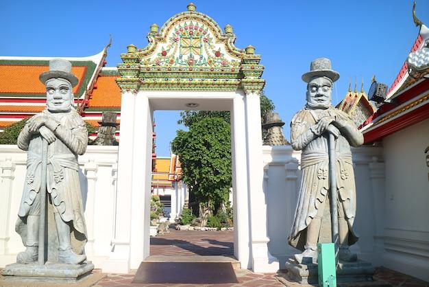 Coppia di statue di guardiani cinesi una volta usate come pietre di zavorra sulle navi secoli fa accanto alla porta ornata del tempio di wat pho, bangkok, thailandia
