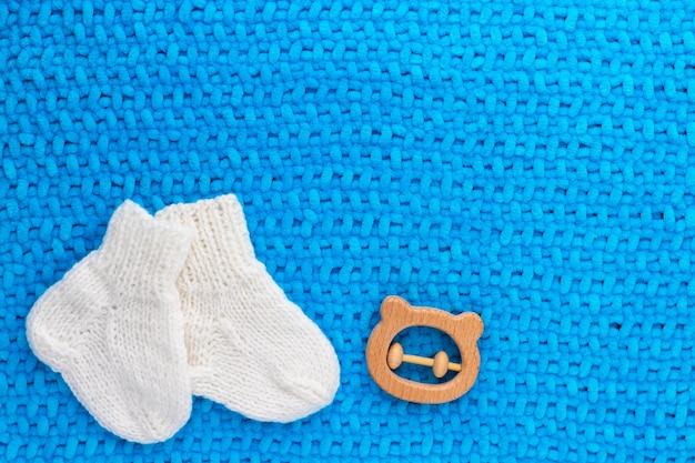 Paio di graziosi calzini bianchi lavorati a maglia e orsacchiotto in legno su plaid blu