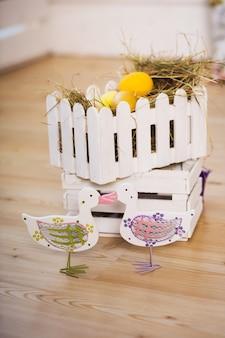 Una coppia di anatre decorative sullo sfondo del nido con le uova di pasqua. sfondo di pasqua.