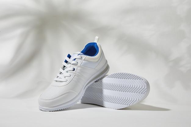 Paio di scarpe da ginnastica alla moda di moda e ombra di foglie di palma su un muro bianco. scarpe sportive da corsa con dettagli in pelle.