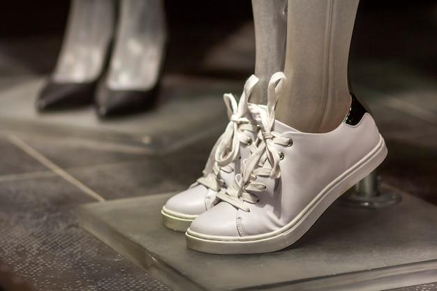 Paia delle scarpe da tennis femminili correnti delle scarpe di sport bianco leggero di cuoio comodo alla moda isolate sul fondo dello scaffale del negozio. stile, design e moda, calzature moderne per palestra e allenamento estivo.