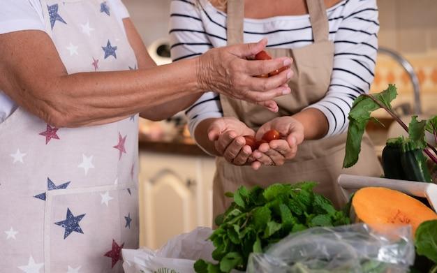 Coppia di mani femminili che tengono pomodorini. un mix di verdure fresche sul tavolo della cucina