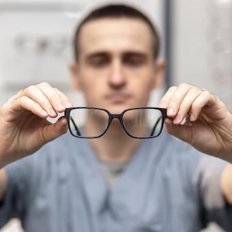 Paio di occhiali tenuti da un uomo sfocato