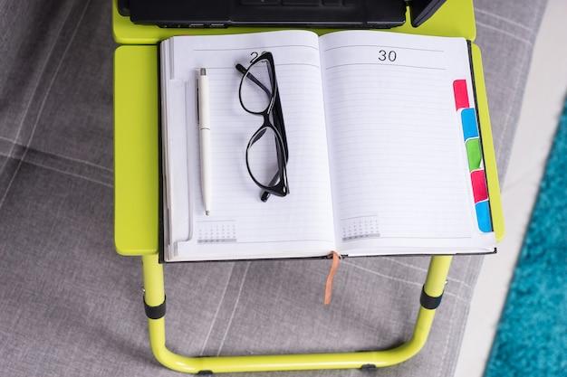 Paio di occhiali sdraiato sulla pagina vuota aperta di un diario aziendale o di un diario con una penna per fissare appuntamenti, organizzare un programma o un'agenda