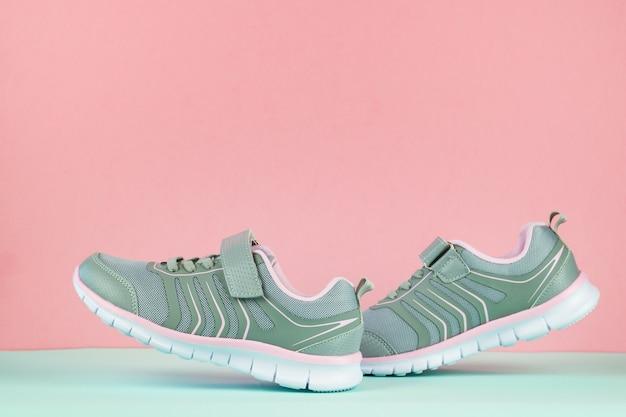 Un paio di scarpe da ginnastica da passeggio grigie su un pavimento blu su una superficie rosa