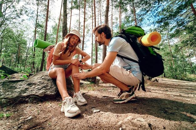 Una coppia di escursionisti con zaini nel bosco. la donna si è fatta male alla gamba, ha sentito dolore e si è seduta su una pietra. campeggio, viaggi, escursioni.