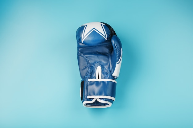 Un paio di guantoni da boxe in pelle su sfondo blu, spazio libero