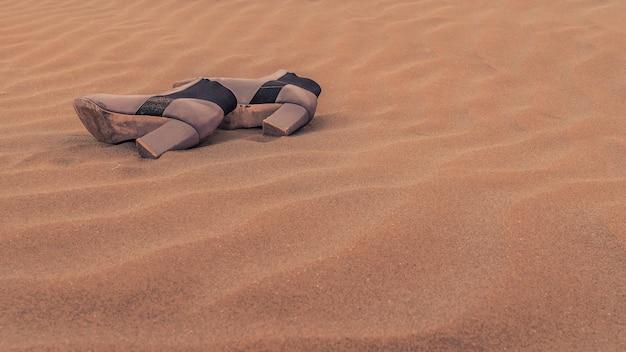 Un paio di scarpe da donna smarrite sulla sabbia tra le dune