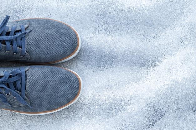Un paio di scarpe da uomo, sneakers in denim blu, comode calzature in tessuto. moda casual