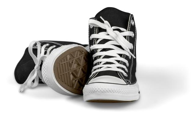 Coppia di nuove scarpe da ginnastica nere isolate su priorità bassa.