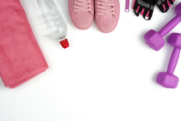 Paio di sneaker in pelle rosa, manubri in plastica e guanti per lo sport