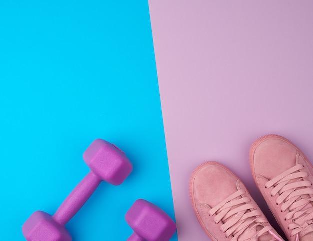 Paio di scarpe da ginnastica in pelle rosa, manubri in plastica per lo sport su uno sfondo blu rosa, sfondo sportivo, vista dall'alto, spazio di copia