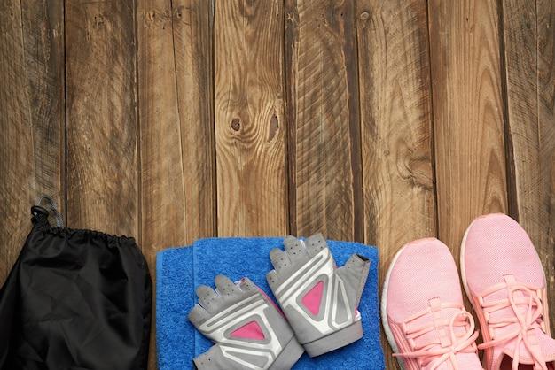 Paio di scarpe da ginnastica rosa, asciugamano blu e guanti per lo sport