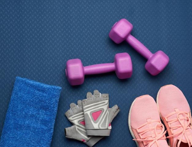 Paio di manubri viola, guanti sportivi e scarpe da ginnastica rosa su un tappetino in neoprene blu