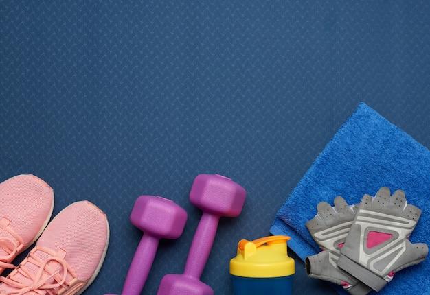 Paio di manubri viola, guanti sportivi e scarpe da ginnastica rosa