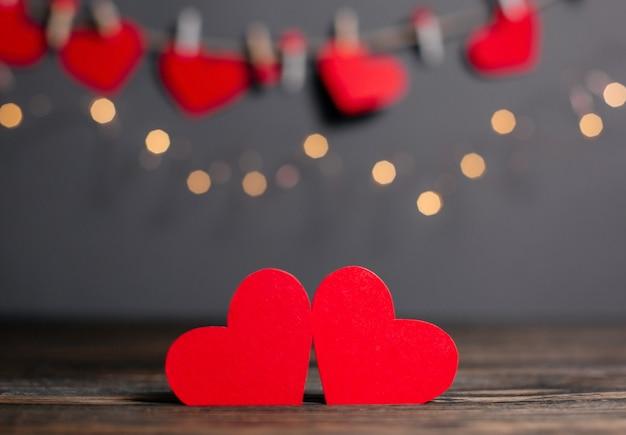 Coppia di cuori rossi su sfondo di luci, amore e concetto di san valentino su un tavolo di legno