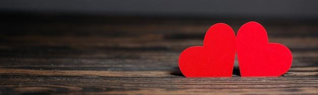 Coppia di cuori rossi su sfondo di legno, amore e concetto di san valentino su un tavolo di legno