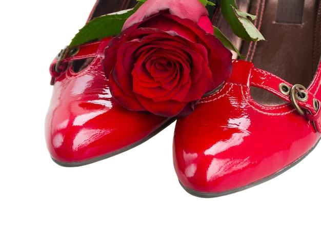 Paio di scarpe rosse con fiore di rosa vicino isolato su sfondo bianco