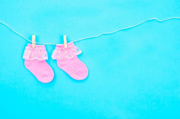 Paio di calzini per bambini carini rosa appesi al filo del bucato su sfondo blu. accessori per bambini. disposizione piatta.