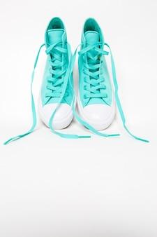 Paio di scarpe con lunghi lacci sciolti su bianco