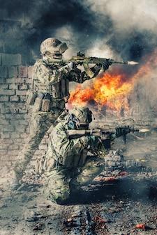 Coppia di forze speciali che sparano a un'arma. fratelli d'armi in azione. pistole in fiamme, muri in rovina di edifici, esplosioni, spari e fumo sullo sfondo