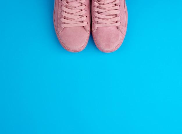 Paio di sneaker sportive rosa con lacci su sfondo blu