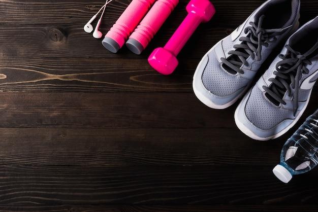 Coppia scarpe sportive, cuffie, manubri e bottiglia d'acqua sul tavolo di legno nero