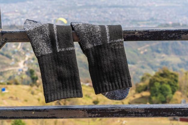 Coppia di calze da trekking che si asciugano sulla recinzione metallica. concetto di attività di trekking ed escursionismo. primo piano foto d'archivio.