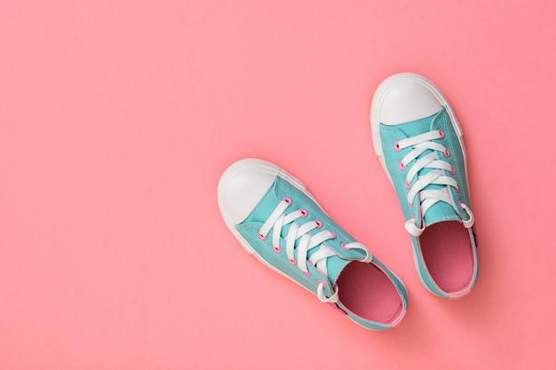 Paio di sneakers turchesi con solette rosa su sfondo rosa. . stile sportivo. lay piatto. la vista dall'alto.