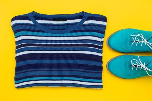 Paio di scarpe in camoscio turchese. stringate acqua di mezza stagione con lacci bianchi e pullover da donna a righe in maglia su fondo giallo