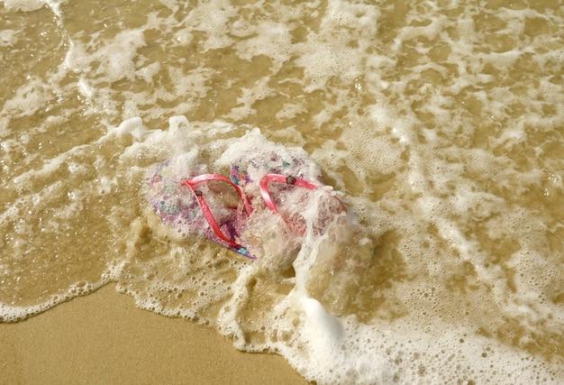 Paio di sandali infradito rosa vibranti sulla spiaggia che si infrangono dalle onde del mare