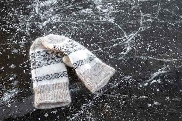 Paio di guanti caldi di lana giace sul ghiaccio