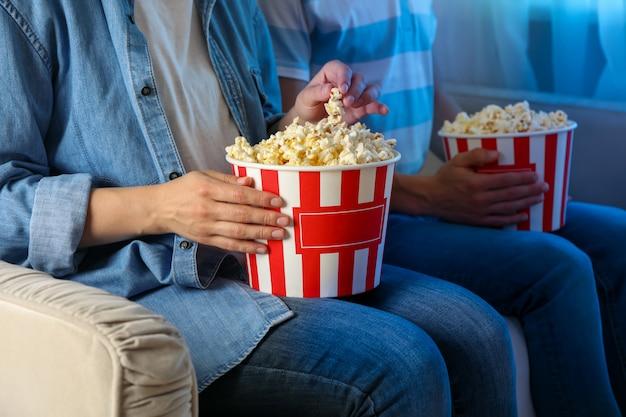 Coppia guarda film sul divano e mangia popcorn. cibo per guardare film