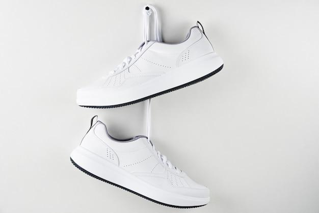 Paio di scarpe da ginnastica maschili bianche appese al muro