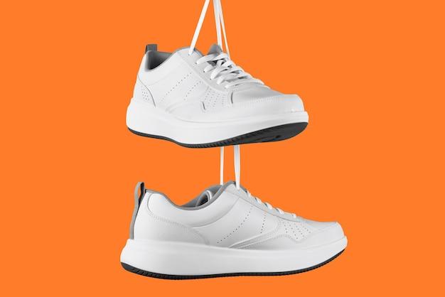 Paio di scarpe da ginnastica maschio bianco su sfondo arancione. scarpe alla moda isolate