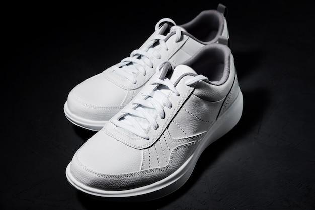 Paio di scarpe da ginnastica bianche su sfondo nero, da vicino