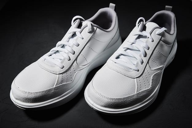 Paio di scarpe da ginnastica bianche isolate sul nero